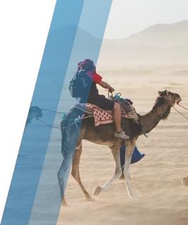 A boy riding a camel in a desert